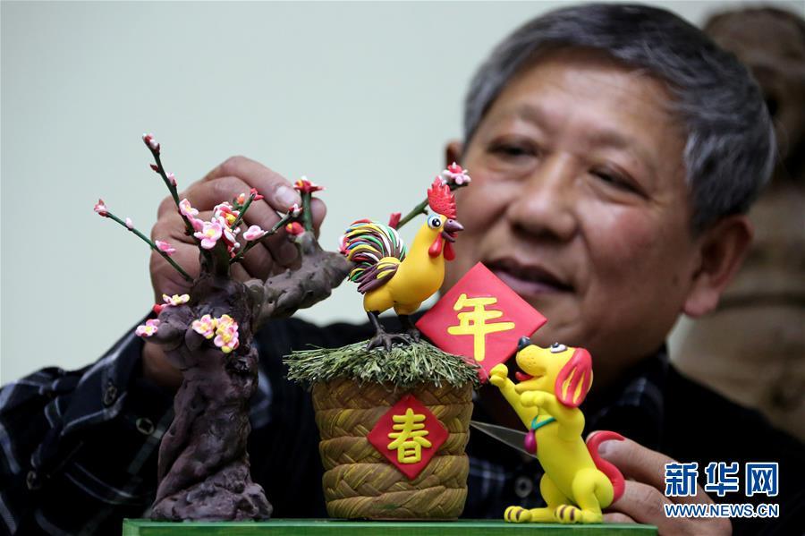 """1月21日,山东省枣庄市市中区民间艺人阚宗勤对面塑作品""""玉犬送金鸡""""进行修整。"""