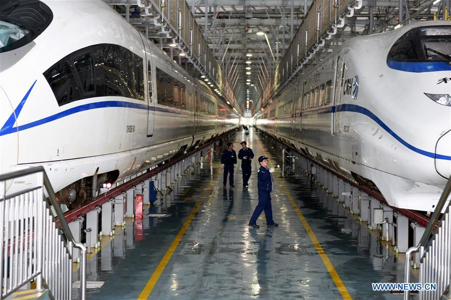 Staff workers check bullet trains for temporary stop at a maintenance station in Hefei, east China's Anhui Province, Jan. 25, 2018. Snow has disrupted railway transportation in some areas of Anhui since Jan. 24. Some trains influenced by the snowfall stopped at the maintenance station in Hefei for power supply and winter protection. (Xinhua/Guo Chen)<br/>