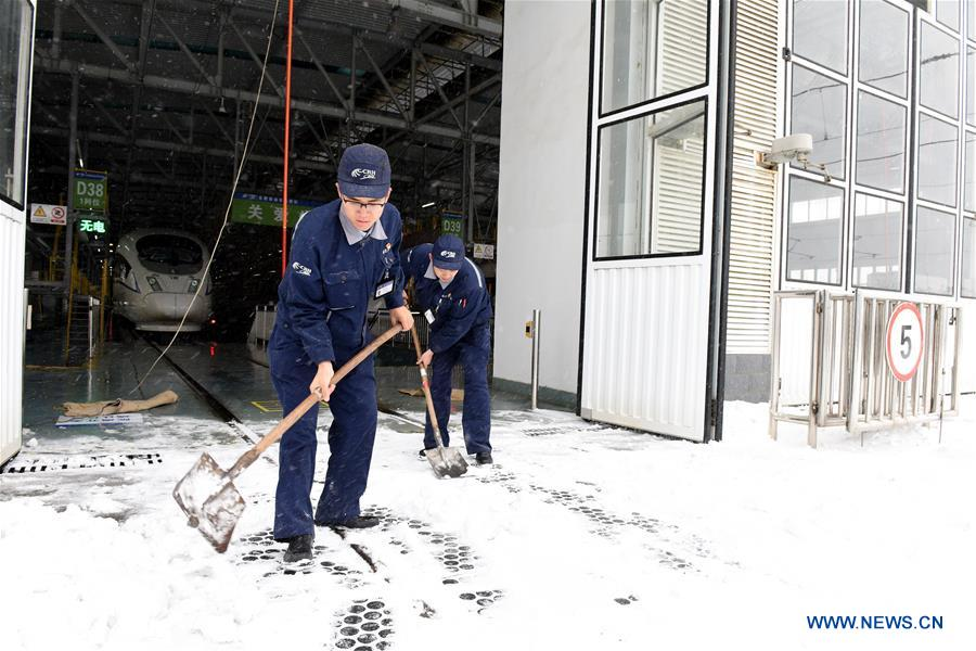 Staff workers sweep snow at a bullet train maintenance station in Hefei, east China's Anhui Province, Jan. 25, 2018. Snow has disrupted railway transportation in some areas of Anhui since Jan. 24. Some trains influenced by the snowfall stopped at the maintenance station in Hefei for power supply and winter protection. (Xinhua/Guo Chen)