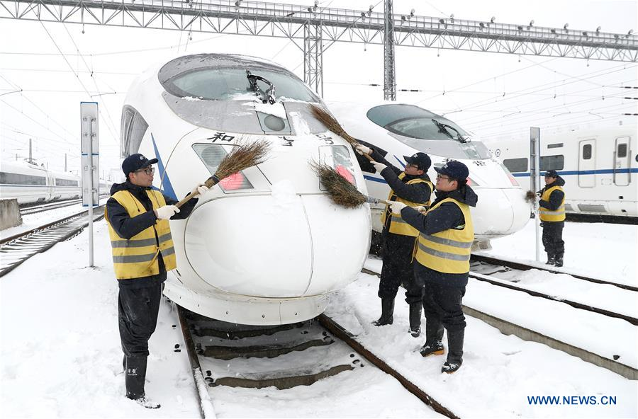 Staff workers sweep snow covered on a bullet train for temporary stop at a maintenance station in Hefei, east China's Anhui Province, Jan. 25, 2018. Snow has disrupted railway transportation in some areas of Anhui since Jan. 24. Some trains influenced by the snowfall stopped at the maintenance station in Hefei for power supply and winter protection. (Xinhua/Guo Chen)<br/>