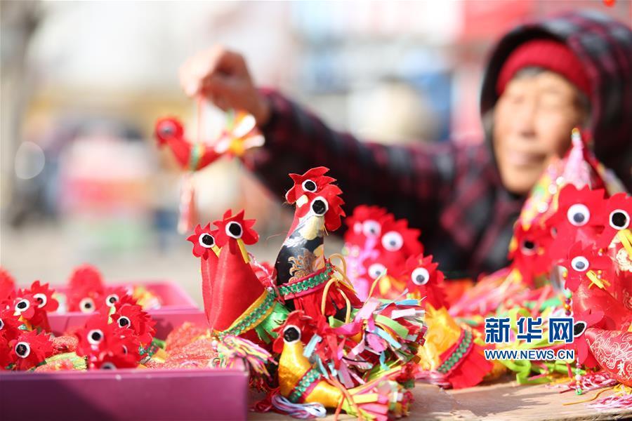 1月30日,一名民间手工艺人在山东省临沂市郯城县街头售卖自己缝制的春鸡。