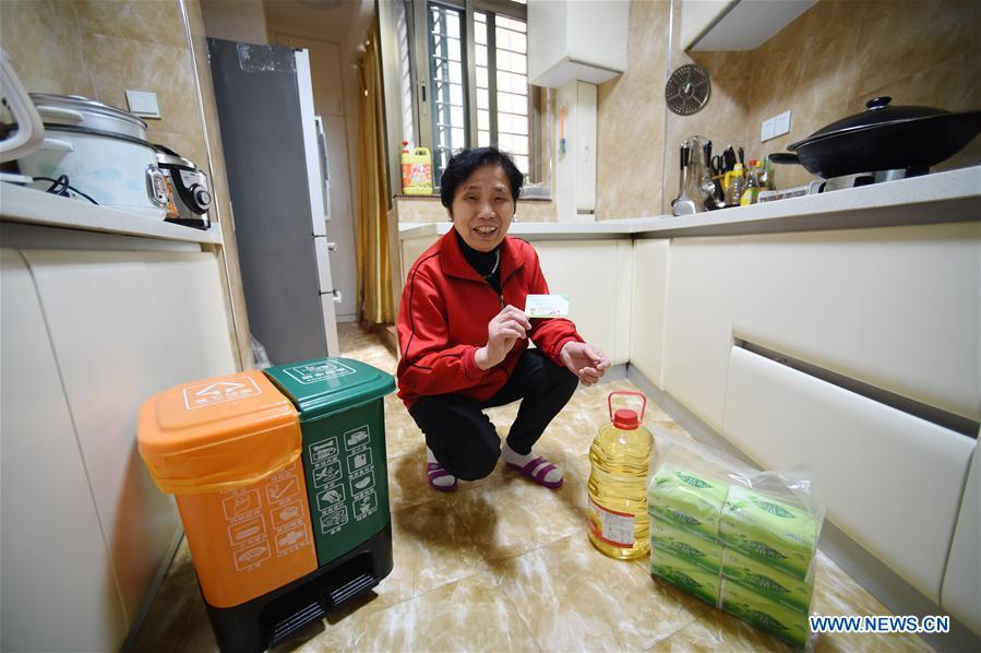 Resident Qiu Caixian shows the point card of garbage classification and items exchanged with the points at her home in Xiamen, southeast China's Fujian Province, March 29, 2017. China's annual political sessions of the National People's Congress (NPC) and the National Committee of the Chinese People's Political Consultative Conference (CPPCC) are scheduled to convene in March, 2018. During the two sessions, development agendas will be reviewed and discussed, and key policies will be adopted. Year 2018 marks the first year of fully implementing the spirit of the 19th National Congress of the Communist Party of China, which vowed to pursue the vision of innovative, coordinated, green, and open development that is for everyone. The CPC congress stressed that building an ecological civilization is vital to sustain the Chinese nation's development, &quot;we must realize that lucid waters and lush mountains are invaluable assets.&quot; (Xinhua/Jiang Kehong)<br/>