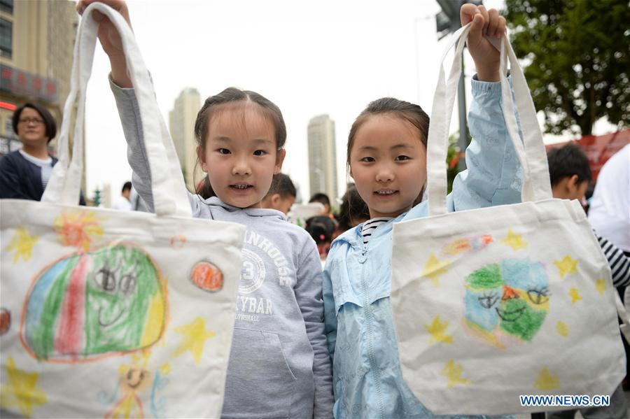 Children show their environment-friendly bags with hand drawings in Tian'ehu community in Hefei, east China's Anhui Province, April 19, 2017. China's annual political sessions of the National People's Congress (NPC) and the National Committee of the Chinese People's Political Consultative Conference (CPPCC) are scheduled to convene in March, 2018. During the two sessions, development agendas will be reviewed and discussed, and key policies will be adopted. Year 2018 marks the first year of fully implementing the spirit of the 19th National Congress of the Communist Party of China, which vowed to pursue the vision of innovative, coordinated, green, and open development that is for everyone. The CPC congress stressed that building an ecological civilization is vital to sustain the Chinese nation's development, &quot;we must realize that lucid waters and lush mountains are invaluable assets.&quot; (Xinhua/Zhang Duan)<br/>