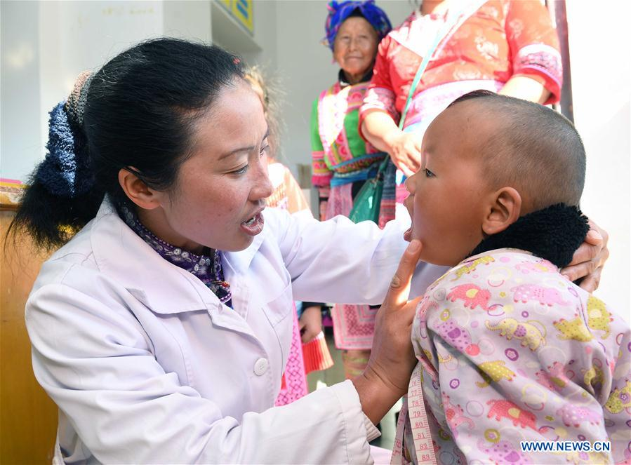 Doctor Yang Lianying of Miao ethnic group, a newly-elected deputy to the 13th National People's Congress, examines health for a child at the village clinic in Henan Village of Xinhua Township in Pingbian Miao Autonomous County of southwest China's Yunnan Province, Feb. 24, 2018. Yang believes that green development should be focused on during the poverty alleviation in remote mountainous areas. China's annual political sessions of the National People's Congress (NPC) and the National Committee of the Chinese People's Political Consultative Conference (CPPCC) are scheduled to convene in March, 2018. During the two sessions, development agendas will be reviewed and discussed, and key policies will be adopted. Year 2018 marks the first year of fully implementing the spirit of the 19th National Congress of the Communist Party of China, which vowed to pursue the vision of innovative, coordinated, green, and open development that is for everyone. The CPC congress stressed that building an ecological civilization is vital to sustain the Chinese nation's development, &quot;we must realize that lucid waters and lush mountains are invaluable assets.&quot; (Xinhua/Yang Zongyou)<br/>