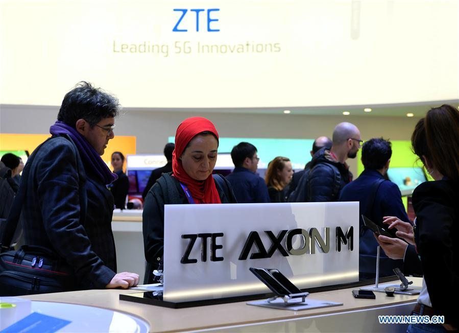People try ZTE AXON M dual-screen smartphones during the closing day of the 2018 Mobile World Congress (MWC) in Barcelona, Spain, on March 1, 2018. The four-day 2018 MWC closed here on Thursday. (Xinhua/Guo Qiuda)<br/>