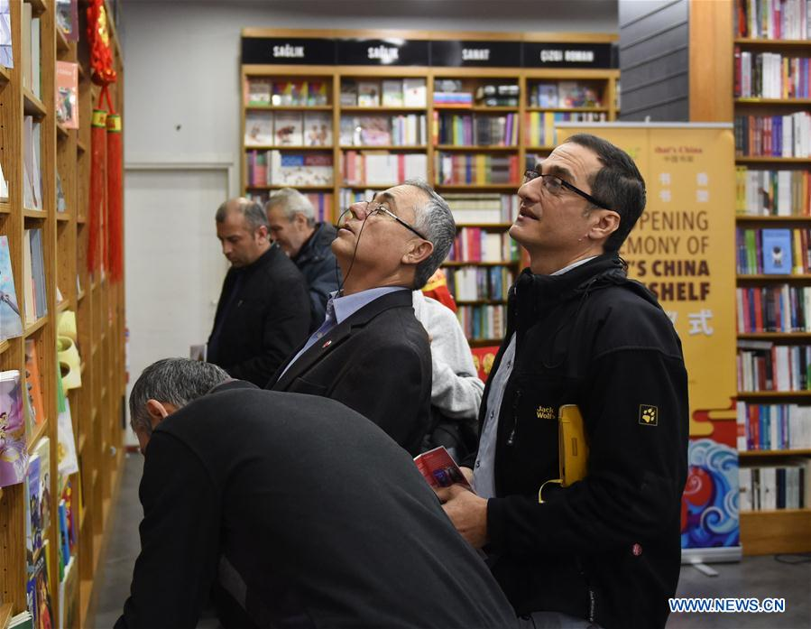 Turkish readers select books in front of China Bookshelf at a Nezih bookstore in Istanbul, Turkey, on March 7, 2018. More than 200 books were put up for sale on the China Bookshelf that was opened Wednesday in a Nezih bookstore in Istanbul, as part of the efforts to promote cultural exchanges between China and Turkey. (Xinhua/He Canling)