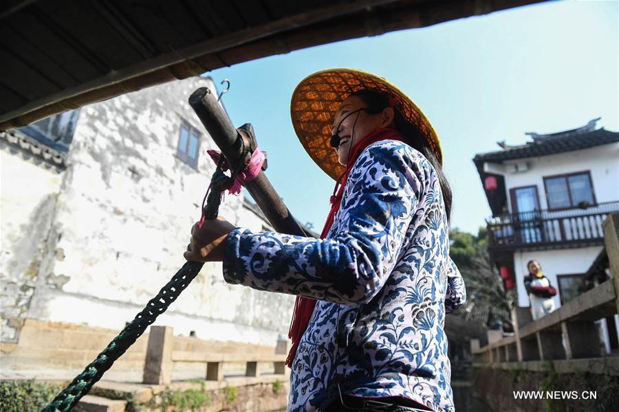 A barge-woman rows a sightseeing boat on the river in the ancient town of Zhouzhuang in Suzhou City, east China's Jiangsu Province, March 10, 2018. As temperature rises, the water town of Zhouzhuang becomes hot tourist destination. (Xinhua/Ji Chunpeng)<br/>