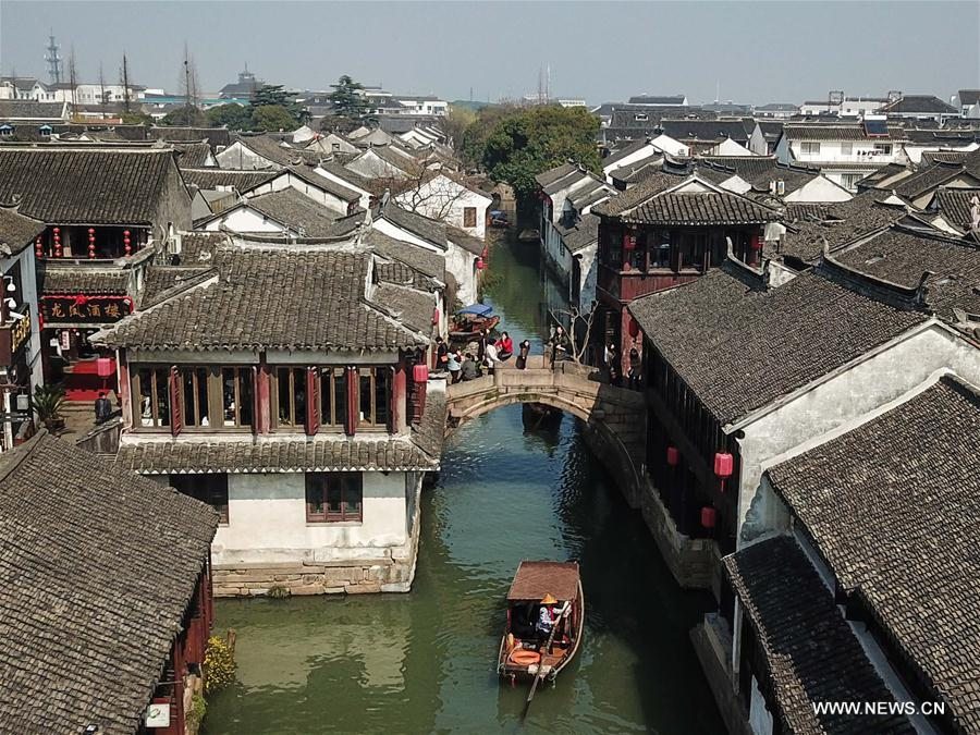 Tourists take sightseeing boats on the river in the ancient town of Zhouzhuang in Suzhou City, east China's Jiangsu Province, March 10, 2018. As temperature rises, the water town of Zhouzhuang becomes hot tourist destination. (Xinhua/Li Bo)<br/>