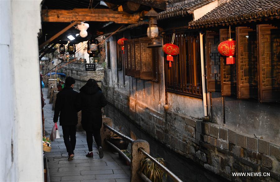 Tourists walk in the ancient town of Zhouzhuang in Suzhou City, east China's Jiangsu Province, March 9, 2018. As temperature rises, the water town of Zhouzhuang becomes hot tourist destination. (Xinhua/Ji Chunpeng)<br/>