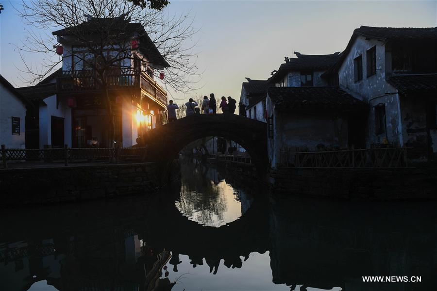 Tourists walk on a bridge in the ancient town of Zhouzhuang in Suzhou City, east China's Jiangsu Province, March 9, 2018. As temperature rises, the water town of Zhouzhuang becomes hot tourist destination. (Xinhua/Ji Chunpeng)<br/>