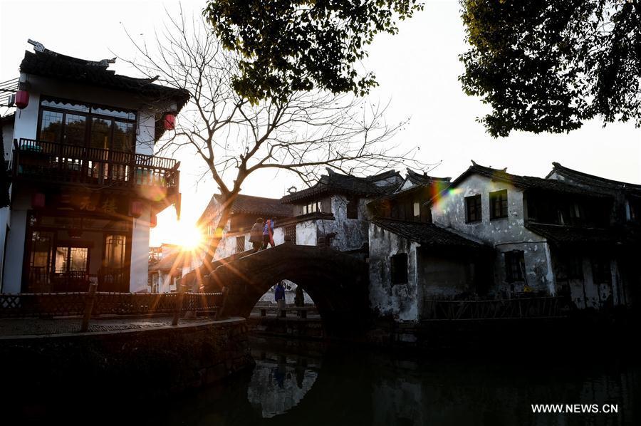 Tourists walk on a bridge in the ancient town of Zhouzhuang in Suzhou City, east China's Jiangsu Province, March 9, 2018. As temperature rises, the water town of Zhouzhuang becomes hot tourist destination. (Xinhua/Li Bo)<br/>