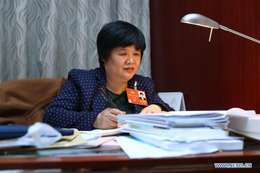Du Liqun takes notes in Beijing, capital of China, March 12, 2018. Du Liqun is a nursing supervisor of AIDS department in the fourth people's hospital of Nanning. She has been stuck to her post ever since the AIDS department was founded in 2005. Apart from management works including the department's regulation making, recruitment and staff training, her major work is to take care of AIDS patients. Over the past years the number of patients she ever nursed exceeds 10,000. In 2015, she was awarded the Florence Nightingale Medal for outstanding contributions to health care. During her long-term medical practice, Du believes that a complete medical service system is indispensable to basic social security. In her spare time, she often provides free diagnosis for people in communities, raising their awareness of health. As a member of the 13th National Committee of the Chinese People's Political Consultative Conference (CPPCC), Du is dedicated to promotion of the primary medical service. She came to this year's CPPCC with a motion to improve medical staff's comprehensive ability of treating infectious diseases. (Xinhua/Zhang Yuwei)<br/>