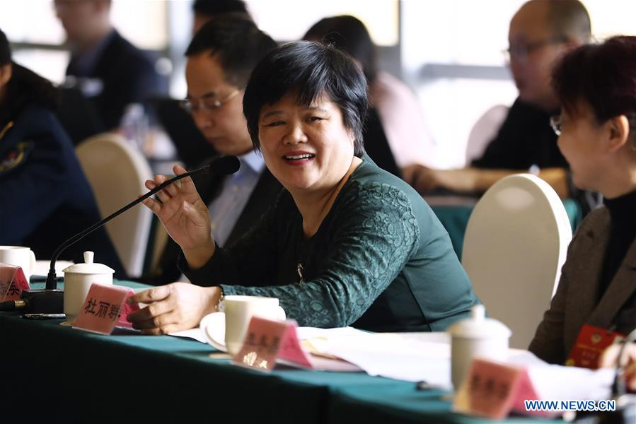 Du Liqun, a member of the 13th National Committee of the Chinese People's Political Consultative Conference (CPPCC), speaks during a panel discussion in Beijing, capital of China, March 12, 2018. Du Liqun is a nursing supervisor of AIDS department in the fourth people's hospital of Nanning. She has been stuck to her post ever since the AIDS department was founded in 2005. Apart from management works including the department's regulation making, recruitment and staff training, her major work is to take care of AIDS patients. Over the past years the number of patients she ever nursed exceeds 10,000. In 2015, she was awarded the Florence Nightingale Medal for outstanding contributions to health care. During her long-term medical practice, Du believes that a complete medical service system is indispensable to basic social security. In her spare time, she often provides free diagnosis for people in communities, raising their awareness of health. As a member of the 13th National Committee of the Chinese People's Political Consultative Conference (CPPCC), Du is dedicated to promotion of the primary medical service. She came to this year's CPPCC with a motion to improve medical staff's comprehensive ability of treating infectious diseases. (Xinhua/Zhang Yuwei)