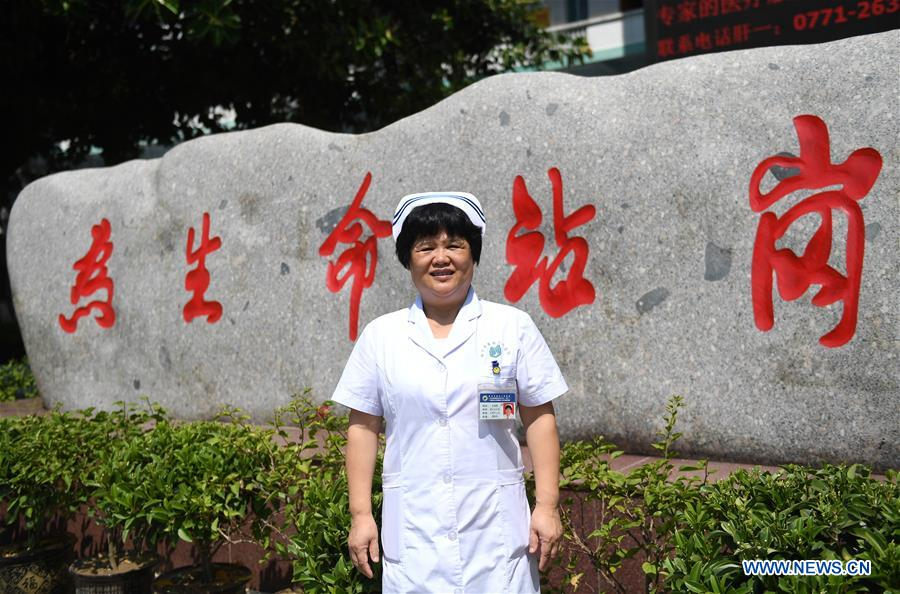 Du Liqun poses for photo in front of the Fourth People's Hospital in Nanning, capital of south China's Guangxi Zhuang Autonomous Region, Sept. 18, 2017. Du Liqun is a nursing supervisor of AIDS department in the fourth people's hospital of Nanning. She has been stuck to her post ever since the AIDS department was founded in 2005. Apart from management works including the department's regulation making, recruitment and staff training, her major work is to take care of AIDS patients. Over the past years the number of patients she ever nursed exceeds 10,000. In 2015, she was awarded the Florence Nightingale Medal for outstanding contributions to health care. During her long-term medical practice, Du believes that a complete medical service system is indispensable to basic social security. In her spare time, she often provides free diagnosis for people in communities, raising their awareness of health. As a member of the 13th National Committee of the Chinese People's Political Consultative Conference (CPPCC), Du is dedicated to promotion of the primary medical service. She came to this year's CPPCC with a motion to improve medical staff's comprehensive ability of treating infectious diseases. (Xinhua/Lu Bo'an)<br/>