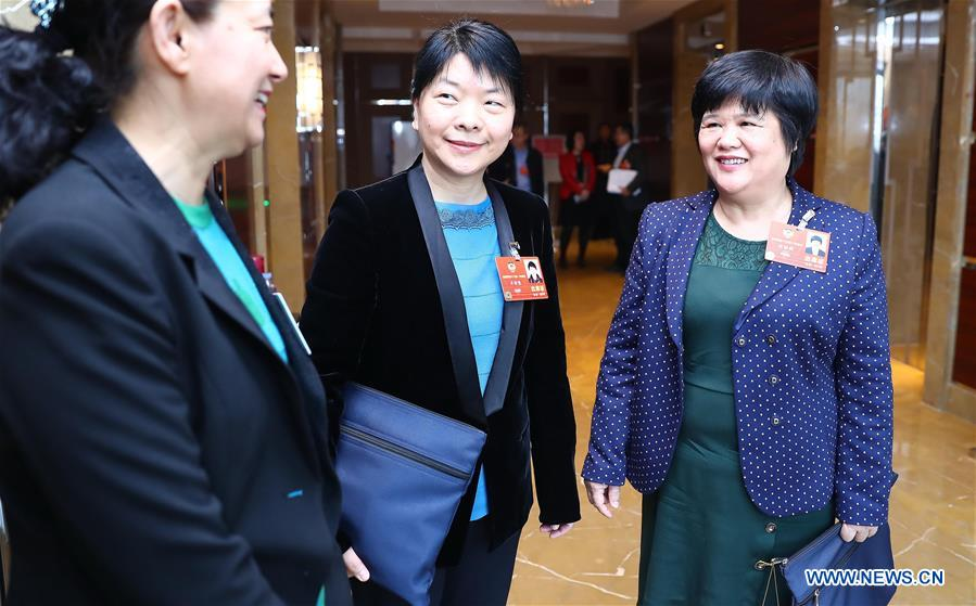 Du Liqun (R), a member of the 13th National Committee of the Chinese People's Political Consultative Conference (CPPCC), talks with other CPPCC members after a panel discussion in Beijing, capital of China, March 12, 2018. Du Liqun is a nursing supervisor of AIDS department in the fourth people's hospital of Nanning. She has been stuck to her post ever since the AIDS department was founded in 2005. Apart from management works including the department's regulation making, recruitment and staff training, her major work is to take care of AIDS patients. Over the past years the number of patients she ever nursed exceeds 10,000. In 2015, she was awarded the Florence Nightingale Medal for outstanding contributions to health care. During her long-term medical practice, Du believes that a complete medical service system is indispensable to basic social security. In her spare time, she often provides free diagnosis for people in communities, raising their awareness of health. As a member of the 13th National Committee of the Chinese People's Political Consultative Conference (CPPCC), Du is dedicated to promotion of the primary medical service. She came to this year's CPPCC with a motion to improve medical staff's comprehensive ability of treating infectious diseases. (Xinhua/Zhang Yuwei)<br/>