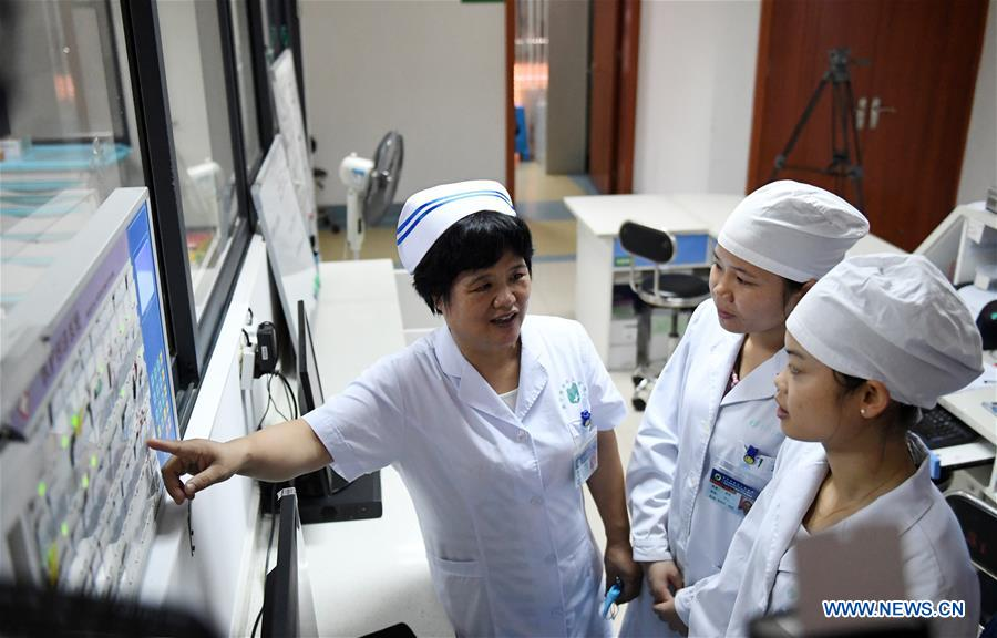 Du Liqun (L) speaks with nurses at the Fourth People's Hospital in Nanning, capital of south China's Guangxi Zhuang Autonomous Region, Sept. 18, 2017. Du Liqun is a nursing supervisor of AIDS department in the fourth people's hospital of Nanning. She has been stuck to her post ever since the AIDS department was founded in 2005. Apart from management works including the department's regulation making, recruitment and staff training, her major work is to take care of AIDS patients. Over the past years the number of patients she ever nursed exceeds 10,000. In 2015, she was awarded the Florence Nightingale Medal for outstanding contributions to health care. During her long-term medical practice, Du believes that a complete medical service system is indispensable to basic social security. In her spare time, she often provides free diagnosis for people in communities, raising their awareness of health. As a member of the 13th National Committee of the Chinese People's Political Consultative Conference (CPPCC), Du is dedicated to promotion of the primary medical service. She came to this year's CPPCC with a motion to improve medical staff's comprehensive ability of treating infectious diseases. (Xinhua/Lu Bo'an)<br/>