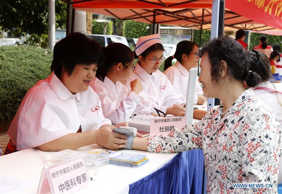 Du Liqun (1st L) measures blood pressure for residents during a free clinic event in Nanning, south China's Guangxi Zhuang Autonomous Region, Nov. 4, 2017. Du Liqun is a nursing supervisor of AIDS department in the fourth people's hospital of Nanning. She has been stuck to her post ever since the AIDS department was founded in 2005. Apart from management works including the department's regulation making, recruitment and staff training, her major work is to take care of AIDS patients. Over the past years the number of patients she ever nursed exceeds 10,000. In 2015, she was awarded the Florence Nightingale Medal for outstanding contributions to health care. During her long-term medical practice, Du believes that a complete medical service system is indispensable to basic social security. In her spare time, she often provides free diagnosis for people in communities, raising their awareness of health. As a member of the 13th National Committee of the Chinese People's Political Consultative Conference (CPPCC), Du is dedicated to promotion of the primary medical service. She came to this year's CPPCC with a motion to improve medical staff's comprehensive ability of treating infectious diseases. (Xinhua/Huang Yumei)<br/>