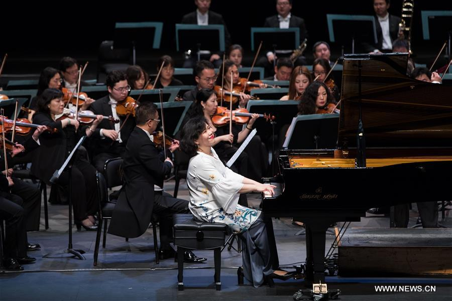 "Malaysian pianist Claudia Yang (front) and musicians of China National Symphony Orchestra perform during the ""Belt and Road"" Malaysia-China friendship piano symphony concert in Istana Budaya in Kuala Lumpur, Malaysia, March 17, 2018. (Xinhua/Zhu Wei)"