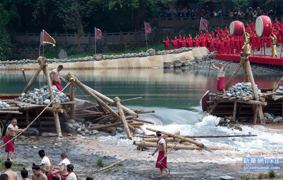 4日、「清明放水節」開幕式で「榪槎」(水止め用の木材の三脚セット)を崩して放水の儀式を行う出演者。(新華社記者/江宏景)<br/>