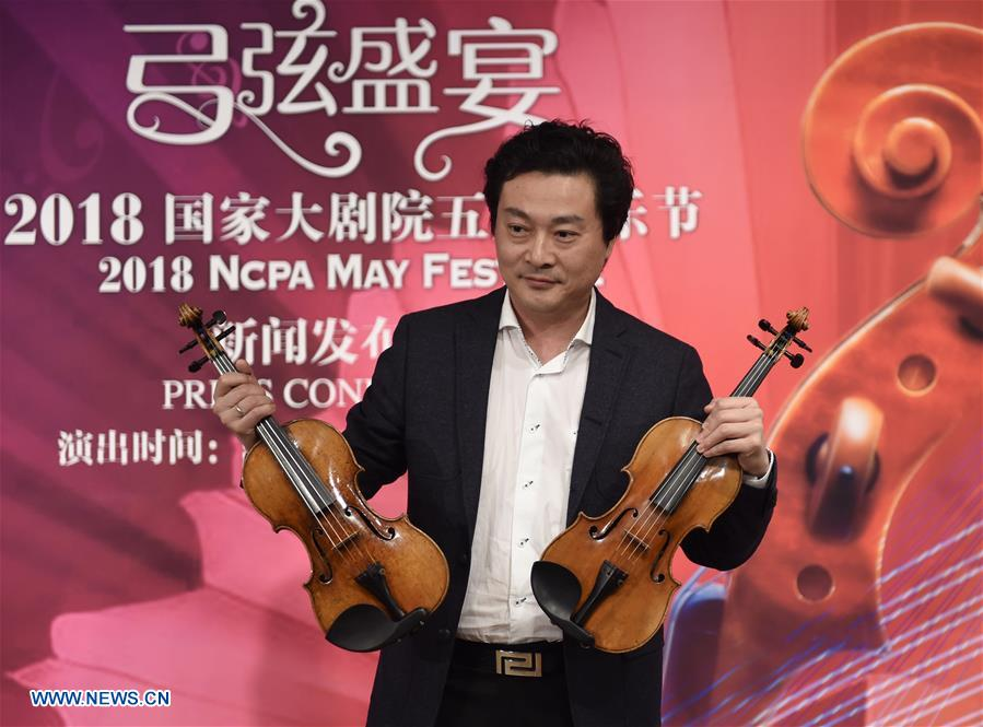 Artist Lyu Siqing displays two violins at a press conference for 2018 May Festival of the National Centre for the Performing Arts (NCPA) in Beijing, capital of China, April 10, 2018. The 2018 NCPA May Festival is scheduled for May 9-26 at the National Centre for the Performing Arts in Beijing. (Xinhua/Luo Xiaoguang)<br/>
