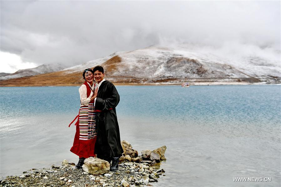 Tourists pose for photos by the Yamdrok Lake in Nagarze County of Shannan City, southwest China's Tibet Autonomous Region, April 8, 2018. The Yamdrok Lake, about 100 kilometers south of the region's capital Lhasa, is one of the three holy lakes in the region. (Xinhua/Zhang Rufeng)<br/>