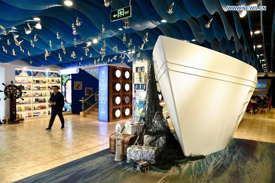 A man walks into the Zhan Qiao Pier Bookstore in Qingdao City, east China's Shandong Province, April 19, 2018. Decorated in an ocean-themed style, the bookstore tries to attract backpackers worldwide and readers who are fond of local gourmet food. (Xinhua/Guo Xulei)