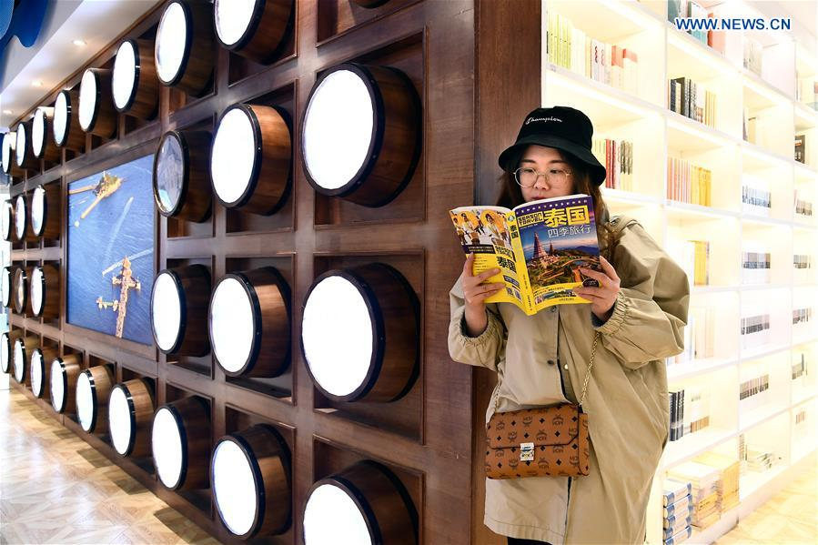 A woman reads a book at the Zhan Qiao Pier Bookstore in Qingdao City, east China's Shandong Province, April 19, 2018. Decorated in an ocean-themed style, the bookstore tries to attract backpackers worldwide and readers who are fond of local gourmet food. (Xinhua/Guo Xulei)<br/>