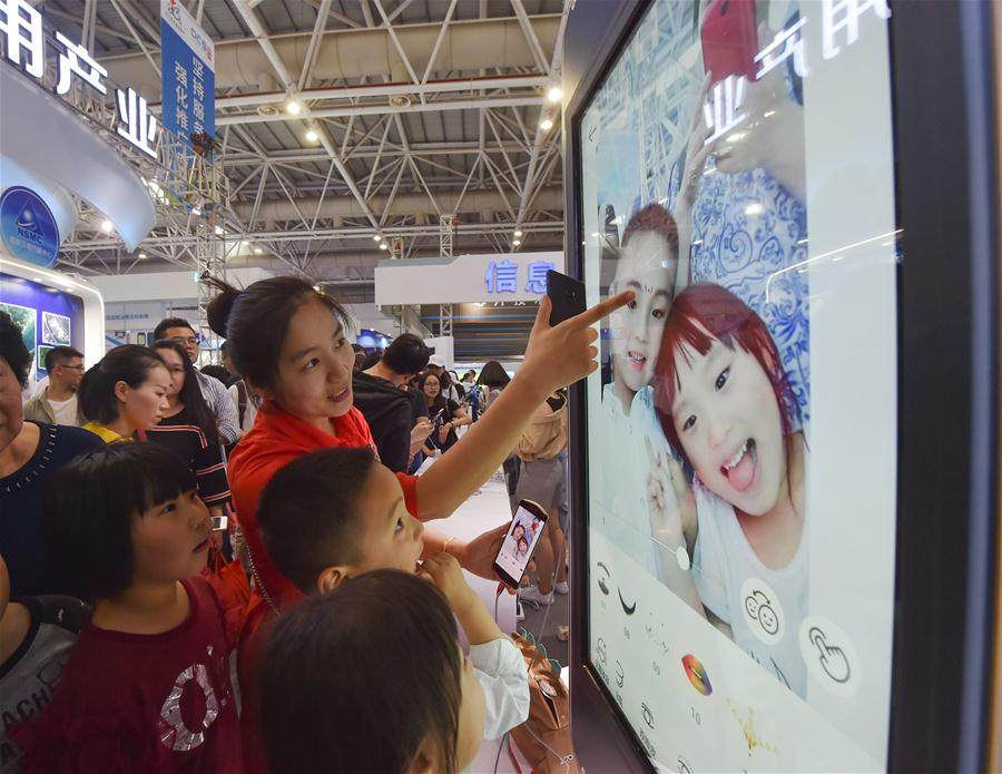 Visitors experience taking selfie with a phone app during the Digital China Exhibition in Fuzhou, capital of southeast China's Fujian Province, April 22, 2018. The exhibition opened to the public on Sunday, during which 293 exhibitors displayed the latest digital technology. (Xinhua/Song Weiwei)<br/>