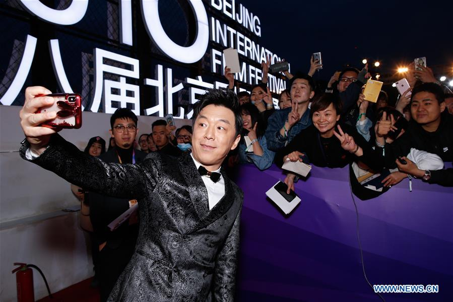 Actor Huang Bo poses for selfie with audience on the red carpet for the closing ceremony of the 8th Beijing International Film Festival (BJIFF) in Beijing, capital of China, April 22, 2018. (Xinhua/Liu Bin)<br/>