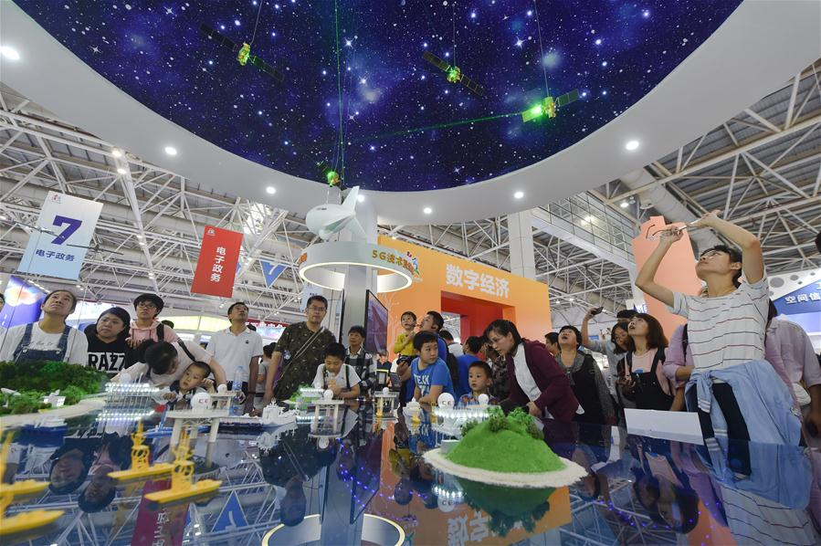 Visitors look at a model of information network during the Digital China Exhibition in Fuzhou, capital of southeast China's Fujian Province, April 22, 2018. The exhibition opened to the public on Sunday, during which 293 exhibitors displayed the latest digital technology. (Xinhua/Song Weiwei)<br/>