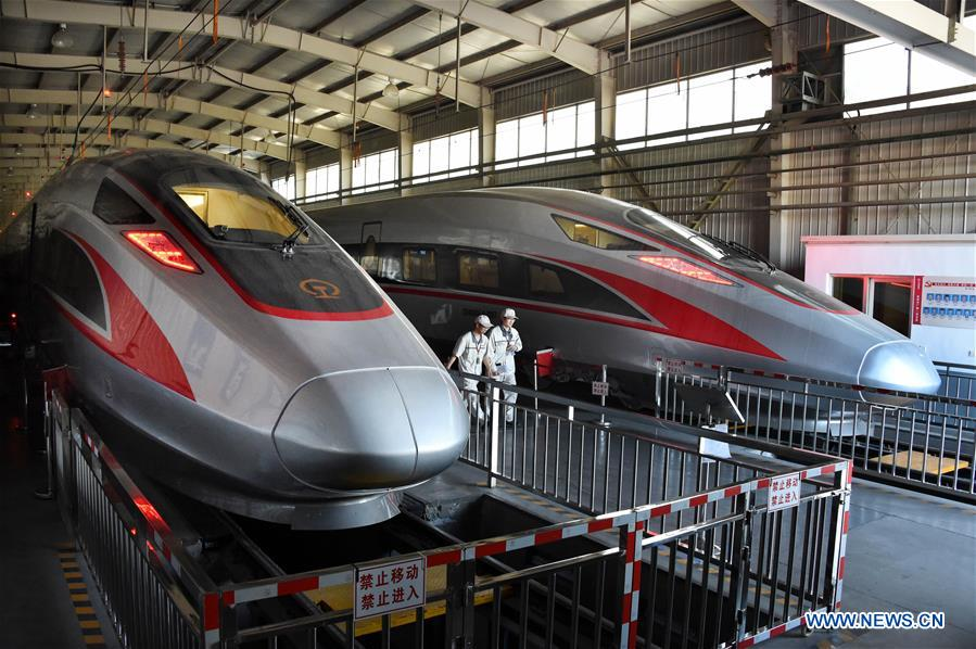 Two 16-carriage Fuxing bullet trains go through a static vehicle testing at a factory in Qingdao, east China's Shandong Province, May 10, 2018. The new 16-carriage longer model of the Fuxing (Rejuvenation) bullet trains is currently under the final static vehicle testing by train maker CRRC in Qingdao. The Fuxing trains are expected to carry twice as many passengers when operations of the new longer model start. (Xinhua/Li Ziheng)<br/>