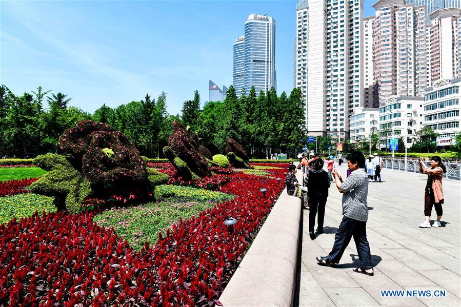 Tourists take photos at the May Fourth Square in Qingdao, east China's Shandong Province, May 31, 2018. The 18th Shanghai Cooperation Organization (SCO) Summit is scheduled for June 9-10 in Qingdao. (Xinhua/Guo Xulei)<br/>