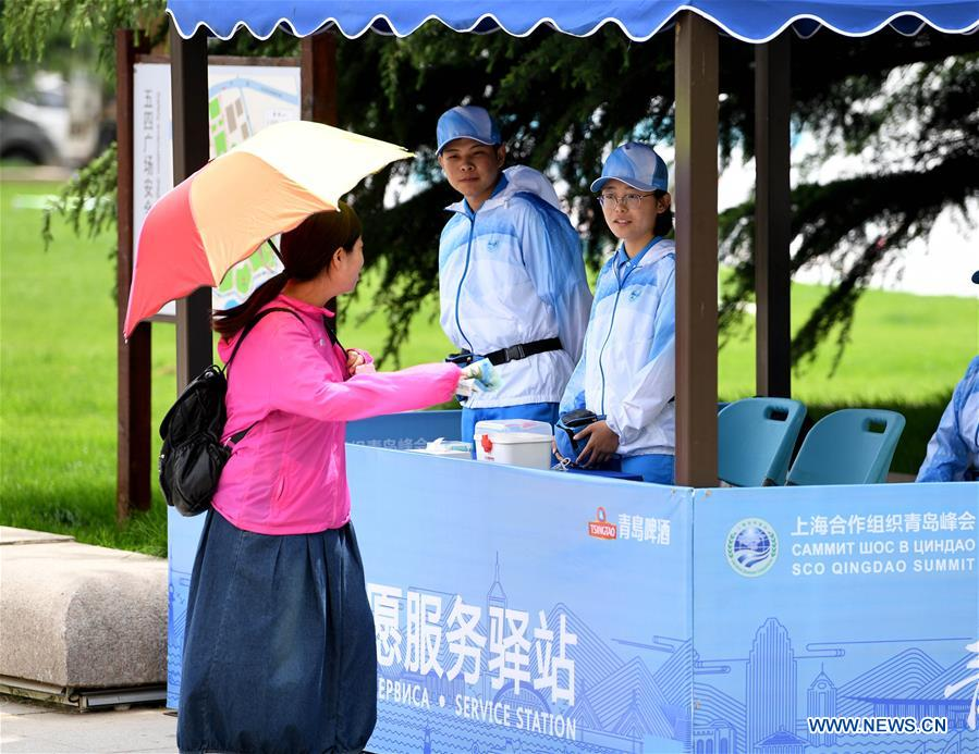 Volunteers give information to tourists at a service station in Qingdao, east China's Shandong Province, June 2, 2018. The 18th Shanghai Cooperation Organization (SCO) Summit is scheduled for June 9-10 in Qingdao. Volunteers are easily seen on the street. (Xinhua/Liu Junxi)<br/>