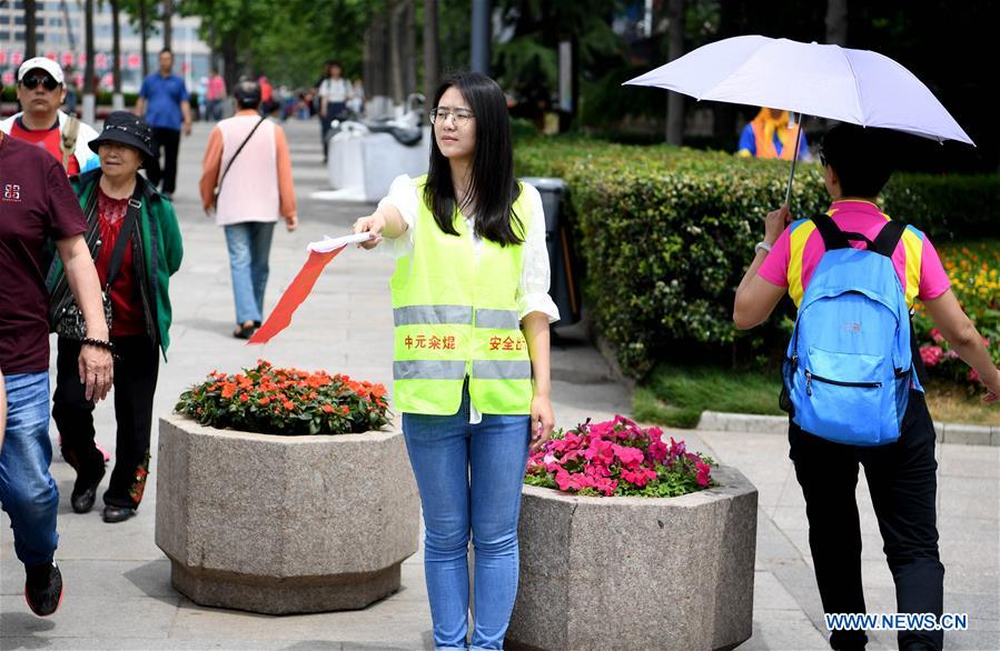 A volunteer guides the tourists near the May Fourth Square in Qingdao, east China's Shandong Province, June 2, 2018. The 18th Shanghai Cooperation Organization (SCO) Summit is scheduled for June 9-10 in Qingdao. Volunteers are easily seen on the street. (Xinhua/Liu Junxi)<br/>