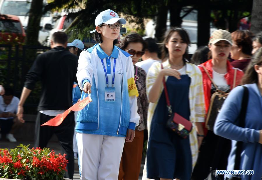 A volunteer guides the pedestrians at a road in Qingdao, east China's Shandong Province, June 2, 2018. The 18th Shanghai Cooperation Organization (SCO) Summit is scheduled for June 9-10 in Qingdao. Volunteers are easily seen on the street. (Xinhua/Li Ziheng)