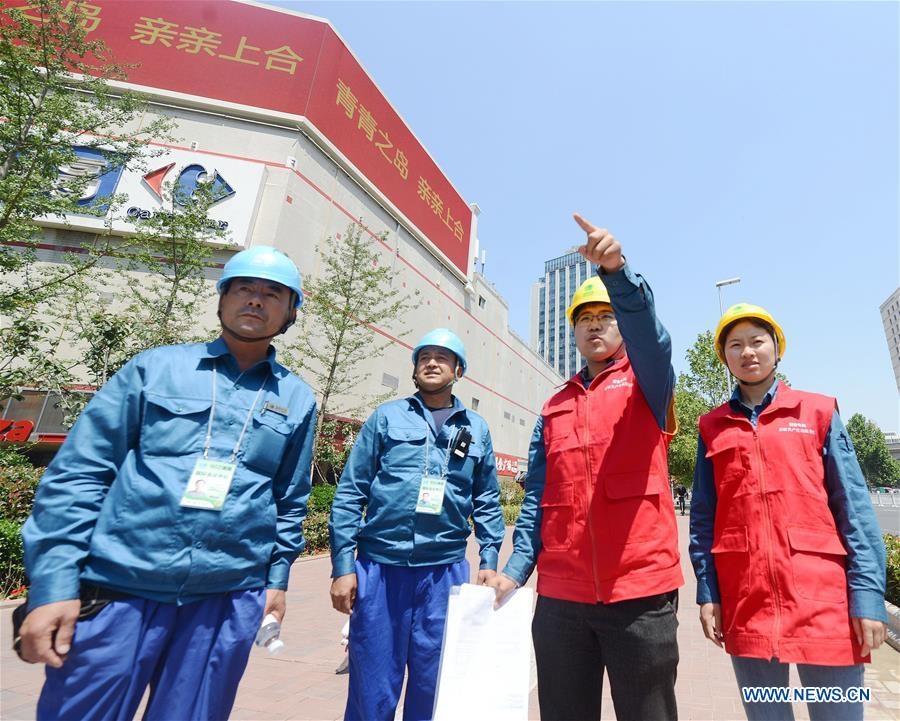 Members of a service team from the State Grid Corporation of China assign works at Nanjing Road in Qingdao, east China's Shandong Province, June 3, 2018. The 18th Shanghai Cooperation Organization (SCO) Summit is scheduled for June 9-10 in Qingdao. Volunteers are easily seen on the street. (Xinhua/Sadat)<br/>