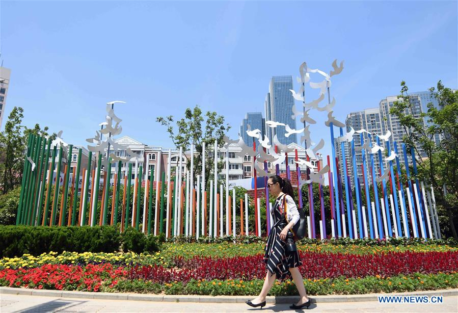 A woman walks past an installation in Qingdao, east China's Shandong Province, June 3, 2018. The 18th Shanghai Cooperation Organization (SCO) Summit is scheduled for June 9 to 10 in Qingdao. (Xinhua/Zhu Zheng)<br/>