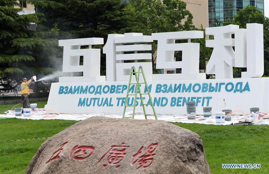 A staff member decorates a sign of Shanghai Cooperation Organization (SCO) Summit in Qingdao, east China's Shandong Province, June 2, 2018. The 18th SCO Summit is scheduled for June 9 to 10 in Qingdao. (Xinhua/Ma Ning)<br/>