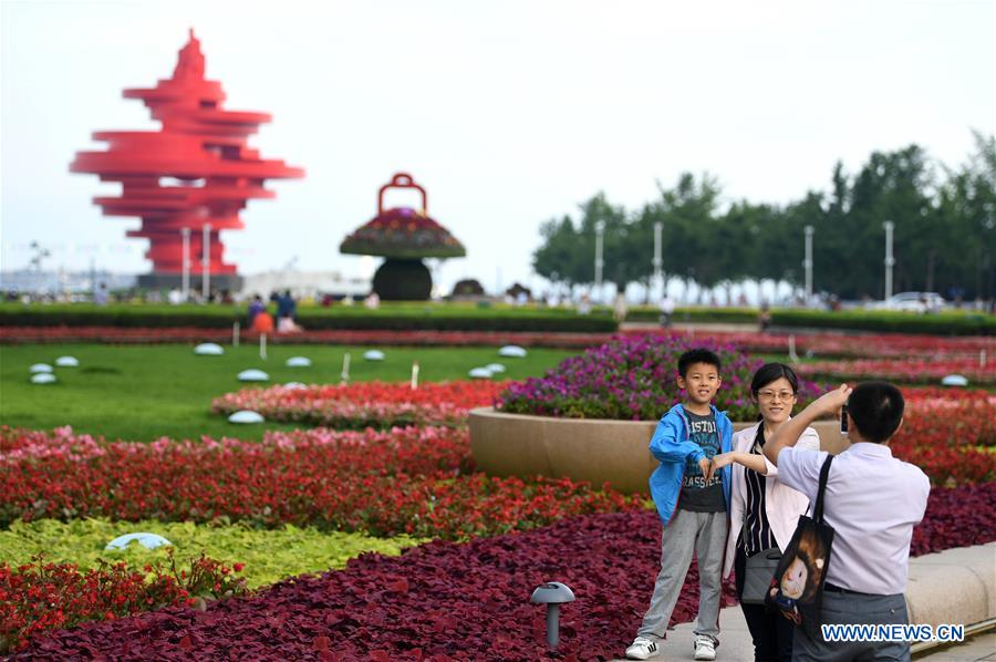 Tourists pose for photo in Qingdao, east China's Shandong Province, June 3, 2018. The 18th Shanghai Cooperation Organization (SCO) Summit is scheduled for June 9 to 10 in Qingdao. (Xinhua/Liu Junxi)<br/>