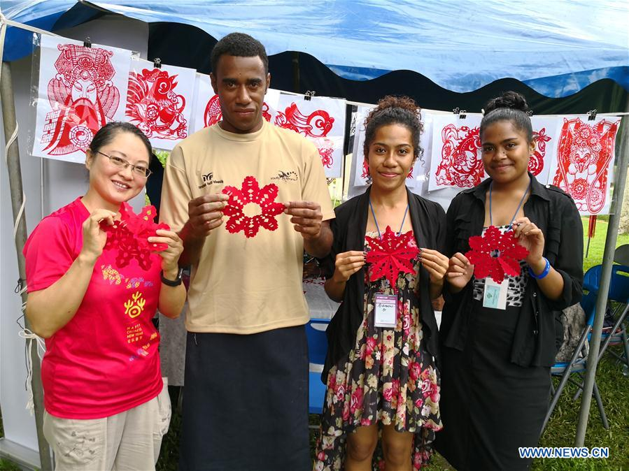 Fijians and a staff member from Fiji China Cultural Centre show their paper-cutting works during the Fiji World Cultural Camp held in Suva, Fiji, June 6, 2018. (Xinhua/Zhang Yongxing)