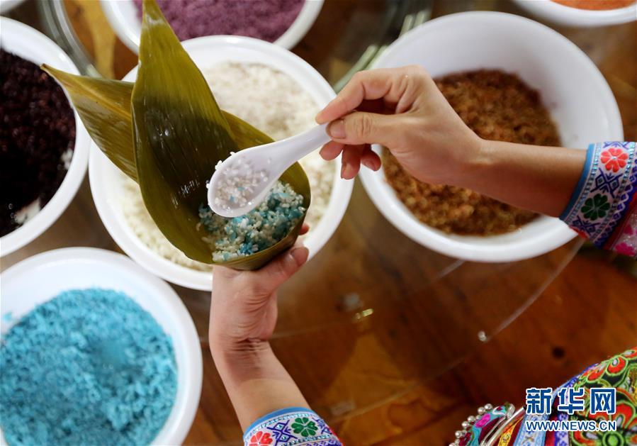 6월 12일 융안현 아요향 주민들이 채색 종자를 만들고 있는 모습이다.<br/>  매년 단오절이 되면 광서(廣西) 류주시(柳州市) 융안현(融安縣) 아요향(雅瑤鄕) 주민들은 화초에서 착즙한 진액을 천연색소로 사용해 다양한 색의 종자를 만들어 먹는다.<br/>