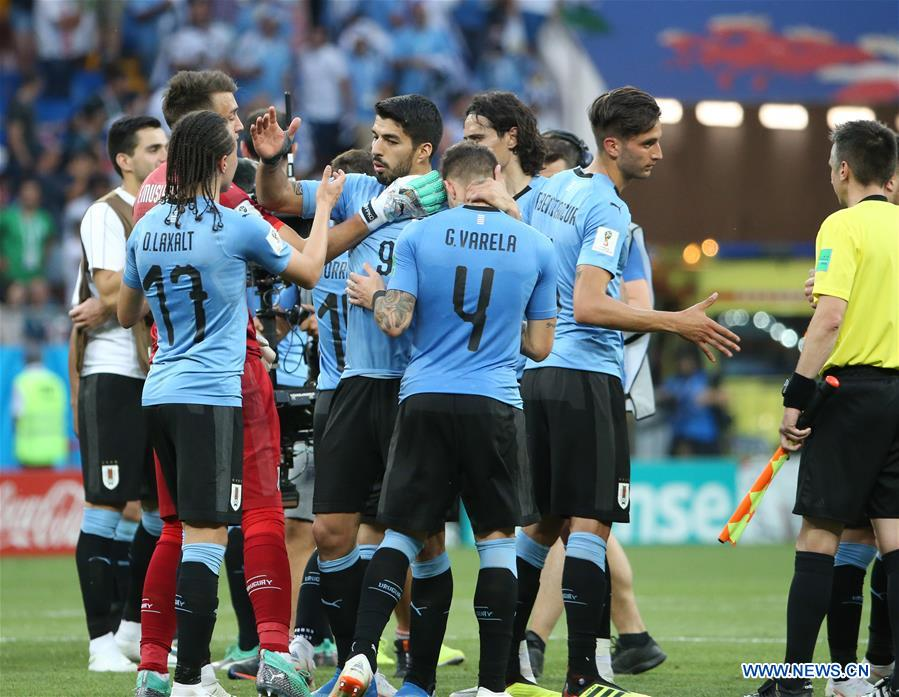 Players of Uruguay celebrate victory after a Group A match between Uruguay and Saudi Arabia at the 2018 FIFA World Cup in Rostov-on-Don, Russia, June 20, 2018. Uruguay won 1-0. (Xinhua/Li Ming)<br/>Uruguay beat Saudi Arabia 1-0 in their World Cup Group A match in the Rostov Arena on Wednesday thanks to a 23rd minute goal from Luis Suarez, who was making his 100th appearance for his country.<br/>Suarez's 52nd international goal means that Uruguay and Russia have both qualified for the knockout stages of the competition, while Saudi Arabia and Egypt are eliminated with one group match still to play.<br/>It was a relatively dull match in Rostov-On-Don with Uruguay happy to control things against a rival who tried hard but lacked the ability to create clear chances against a defense well-marshalled by Diego Godin and Jose Gimenez.<br/>