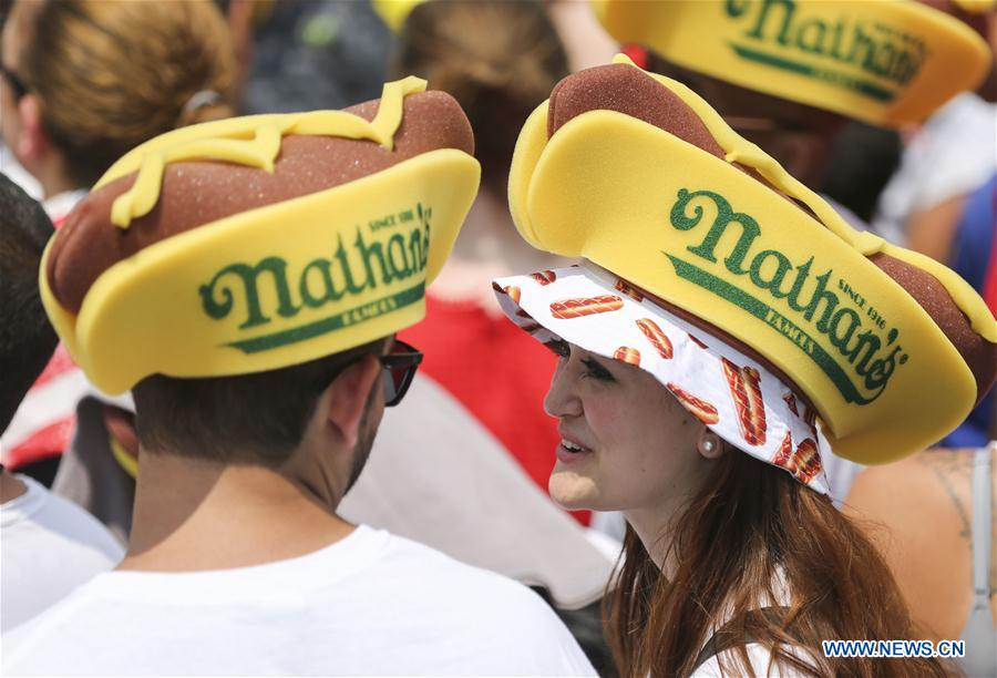 Onlookers wearing hats in the shape of hot dogs watch the Nathan's Hot Dog Eating Contest at Coney Island of New York, the United States, on July 4, 2018. Joey Chestnut set a new world record Wednesday by devouring 74 hot dogs in 10 minutes at the Nathan's Hot Dog Eating Contest in New York. Miki Sudo defended the women's title by eating 37 hot dogs in 10 minutes. (Xinhua/Wang Ying)<br/>