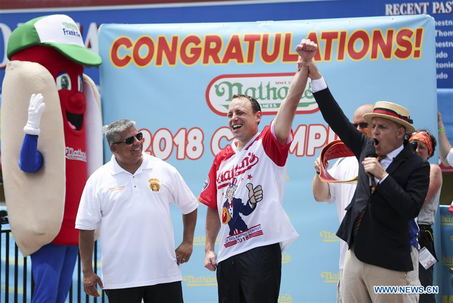 Joey Chestnut (C) celebrates after winning the men's competition of the Nathan's Hot Dog Eating Contest at Coney Island of New York, the United States, on July 4, 2018. Joey Chestnut set a new world record Wednesday by devouring 74 hot dogs in 10 minutes at the Nathan's Hot Dog Eating Contest in New York. Miki Sudo defended the women's title by eating 37 hot dogs in 10 minutes. (Xinhua/Wang Ying)<br/>