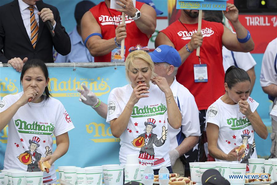 Miki Sudo (C, Front) competes during the women's competition of the Nathan's Hot Dog Eating Contest at Coney Island of New York, the United States, on July 4, 2018. Joey Chestnut set a new world record Wednesday by devouring 74 hot dogs in 10 minutes at the Nathan's Hot Dog Eating Contest in New York. Miki Sudo defended the women's title by eating 37 hot dogs in 10 minutes. (Xinhua/Wang Ying)<br/>