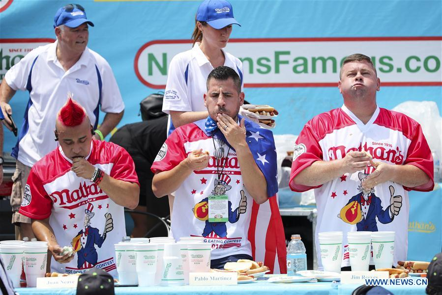 Eaters compete in the men's competition of the Nathan's Hot Dog Eating Contest at Coney Island of New York, the United States, on July 4, 2018. Joey Chestnut set a new world record Wednesday by devouring 74 hot dogs in 10 minutes at the Nathan's Hot Dog Eating Contest in New York. Miki Sudo defended the women's title by eating 37 hot dogs in 10 minutes. (Xinhua/Wang Ying)<br/>