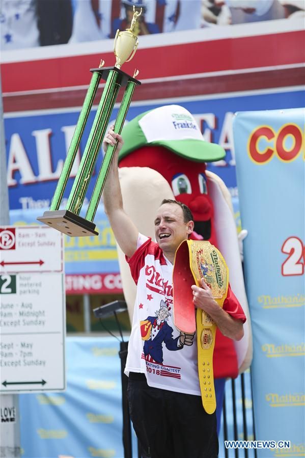 Joey Chestnut celebrates after winning the men's competition of the Nathan's Hot Dog Eating Contest at Coney Island of New York, the United States, on July 4, 2018. Joey Chestnut set a new world record Wednesday by devouring 74 hot dogs in 10 minutes at the Nathan's Hot Dog Eating Contest in New York. Miki Sudo defended the women's title by eating 37 hot dogs in 10 minutes. (Xinhua/Wang Ying)<br/>