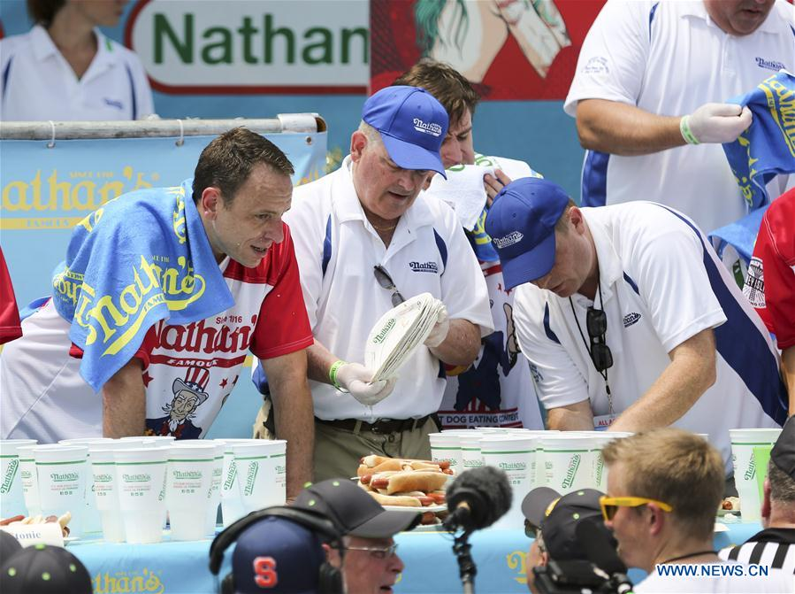 Joey Chestnut (L) and staff members count the plates for holding hot dogs after the men's competition of the Nathan's Hot Dog Eating Contest at Coney Island of New York, the United States, on July 4, 2018. Joey Chestnut set a new world record Wednesday by devouring 74 hot dogs in 10 minutes at the Nathan's Hot Dog Eating Contest in New York. Miki Sudo defended the women's title by eating 37 hot dogs in 10 minutes. (Xinhua/Wang Ying)<br/>