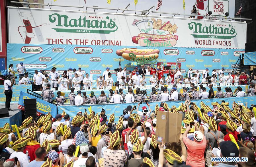 Eaters compete in the women's competition of the Nathan's Hot Dog Eating Contest at Coney Island of New York, the United States, on July 4, 2018. Joey Chestnut set a new world record Wednesday by devouring 74 hot dogs in 10 minutes at the Nathan's Hot Dog Eating Contest in New York. Miki Sudo defended the women's title by eating 37 hot dogs in 10 minutes. (Xinhua/Wang Ying)<br/>
