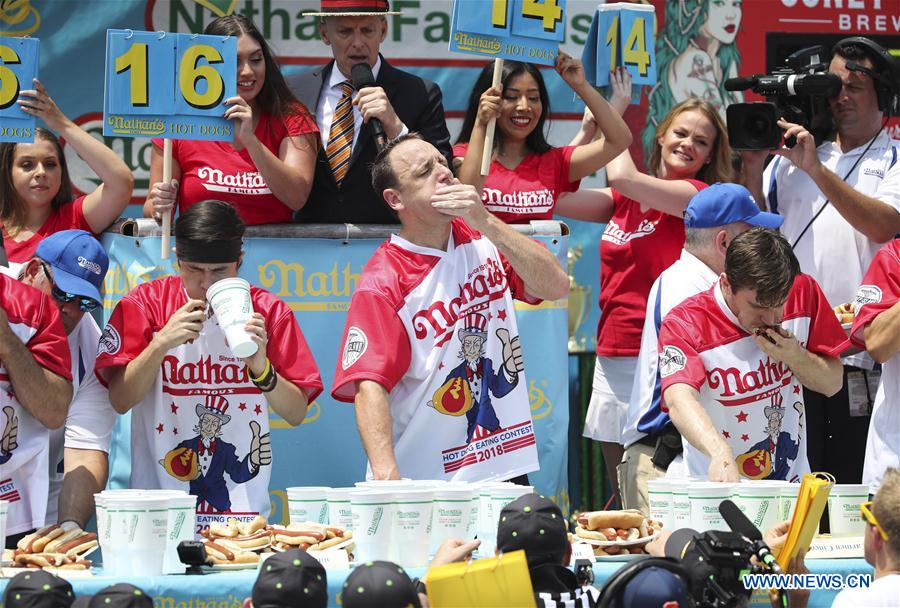 Joey Chestnut (C, Front) competes during the men's competition of the Nathan's Hot Dog Eating Contest at Coney Island of New York, the United States, on July 4, 2018. Joey Chestnut set a new world record Wednesday by devouring 74 hot dogs in 10 minutes at the Nathan's Hot Dog Eating Contest in New York. Miki Sudo defended the women's title by eating 37 hot dogs in 10 minutes. (Xinhua/Wang Ying)<br/>